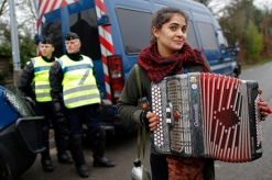 A woman plays the accordion as she arrives to attend a music festival in Notre-Dame-des-Landes